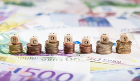 Word Economy on coin stacks, cash background Royalty Free Stock Photos