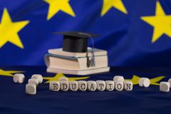 Word  EDUCATION composed of wooden letters. Black graduate hat on EU flag in the background. Closeup royalty free stock photo