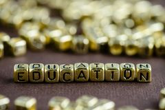 Word EDUCATION made from small golden letters on the brown background, selective focus stock photography