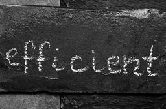 The word efficient written with chalk on black stone. Stock Photography