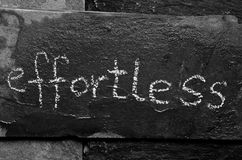 The word effortless written with chalk on black stone. Royalty Free Stock Images