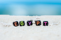 Word Egypt is made of multicolored letters on snow-white sand against the blue sea. Stock Photos