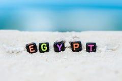 Word Egypte wordt gemaakt van multicolored brieven op sneeuwwit zand tegen het blauwe overzees Stock Foto's