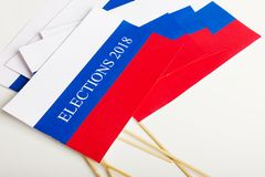 The word election in a small paper flag of Russia. On the table with other flags Stock Photos