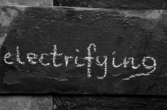 The word electrifying written with chalk on black stone. Stock Image
