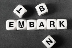 Word embark on toy cubes. Word embark on white toy cubes royalty free stock photo