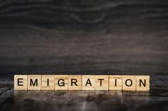 The word emigration is made of bright wood cubes with black letters on a dark wooden background stock images