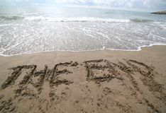 Word THE END written on the sand and the wave that is deleting t. He text can be used for the end of the presentations or at the end of a movie Royalty Free Stock Photos