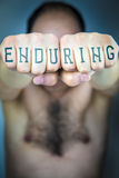 The word ENDURING written on the fists of a man Royalty Free Stock Photo