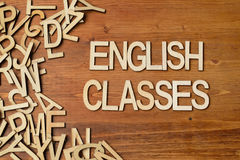 Word english classes. Made with wooden letters on the white plank table Royalty Free Stock Image