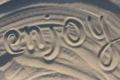 Word enjoy drawn on sand in sunset sunlight as relax and vacation background. Stock Photography