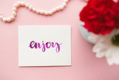 Word Enjoy handwritten in calligraphy style with watercolor. Floral composition on a pale pink pastel background.  Royalty Free Stock Photo