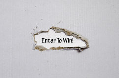 The word enter to win appearing behind torn paper Royalty Free Stock Image