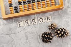 Word ERROR laid out of handwritten letters on cardboard squares near old wooden abacus and three cones. On gray cracked concrete stock images