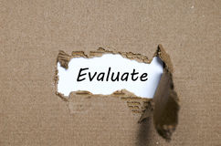 The word evaluate appearing behind torn paper. The word evaluate behind torn paper Stock Images