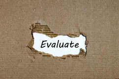 The word evaluate appearing behind torn paper. The word evaluate behind torn paper Stock Photography