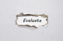 The word evaluate appearing behind torn paper. The word evaluate  behind torn paper Royalty Free Stock Image