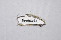 The word evaluate appearing behind torn paper. The word evaluate behind torn paper Stock Photos