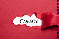 The word evaluate appearing behind torn paper Stock Image