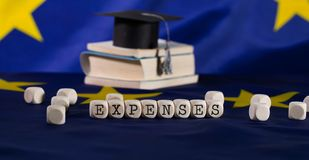 Word EXPENSES composed of wooden letters. Black graduate hat on EU flag in the background. Closeup stock photography