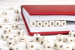 Word Expert written in wooden blocks in notebook on white wooden stock photography