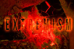 Word extremism written on red hot wood embers detail in fire place.  Stock Images