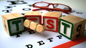 The word eye spelled on a dice falling onto eye test Stock Image