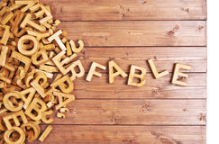 Word fable made with wooden letters. Word fable made with block wooden letters next to a pile of other letters over the wooden board surface composition royalty free stock photo