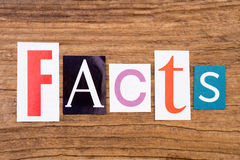 Word `facts` in cut out magazine letters. On wooden background stock images