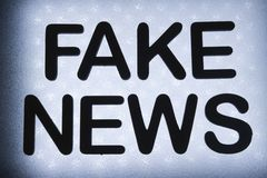 """Word """"fake news"""". Written in wood letters and lit by background in backlight stock photography"""