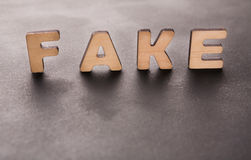 Word Fake standing on table. Background. Lie, not originality, imitation concept Royalty Free Stock Photo