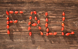 Word FALL made of wild rose hips on  wooden table Stock Photo