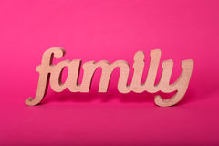 Word family, wooden letters on pink paper background. Love and unity concept. Stock Image