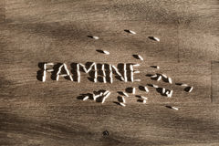 Word famine made of rice. Word famine made of few white rice grains on wooden table - symbol of hunger and scarcity of food Stock Images