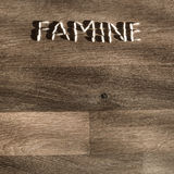Word famine made of rice grains. Word famine made of few white rice grains on wooden table - symbol of hunger and scarcity of food Stock Photo