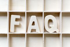 The word FAQ wood in slot, Frequently asked questions. Website stock photography
