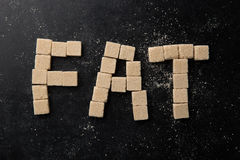 The word fat made of sugar cubes. On table Royalty Free Stock Images