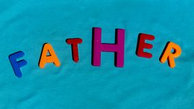The word Father composed from letters. The word Father composed from colorful children toy big letters on the grass royalty free stock photos