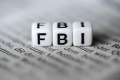 Word FBI formed by wood alphabet blocks on newspaper. Closeup Stock Photo