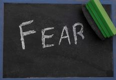 The word FEAR being erased from a chalkboard Stock Images