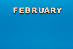 Word February on blue background Royalty Free Stock Photo