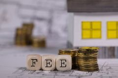 Word FEE composed of wooden letter. Small paper house in the background. Closeup stock photo