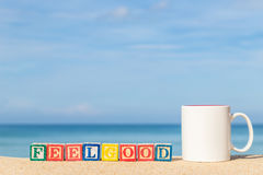 Word FEELGOOD in colorful alphabet blocks on tropical beach Stock Photos