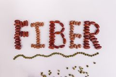 Word FIBER created with pinto red kidney lentil beans. Word FIBER created with raw dry beans pinto dark red kidney lentils on a solid white background royalty free stock images