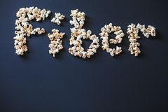 A word `Fiber` made of fresh popcorn on dark matte painted surface. stock photos