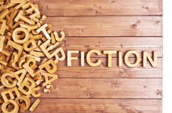 Word fiction made with wooden letters. Word fiction made with block wooden letters next to a pile of other letters over the wooden board surface composition Royalty Free Stock Photo