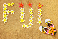 Word Fiji written on a beach with plumeria flowers. Travel concept Royalty Free Stock Image