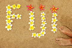 Word Fiji written on a beach with plumeria flowers. Travel concept Stock Photo
