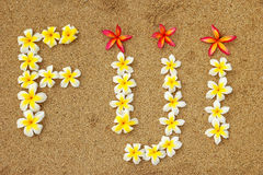 Word Fiji written on a beach with plumeria flowers. Travel concept Royalty Free Stock Images