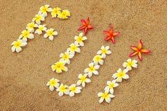 Word Fiji written on a beach with plumeria flowers. Travel concept Stock Photos